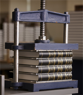 Bindery equipment pressing down on books